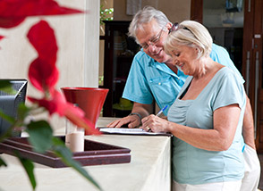 Older couple signing in at front desk