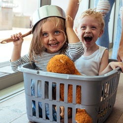 parent pushing kids around in a laundry basket