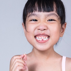 child smiling while holding a tooth they lost