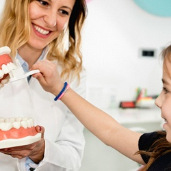 dentist showing child brushing techniques