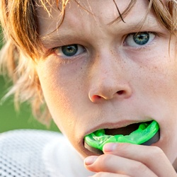 boy inserting green mouthguard