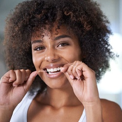 woman smiling while flossing