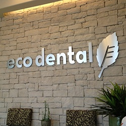 Eco Dental sign on brick wall