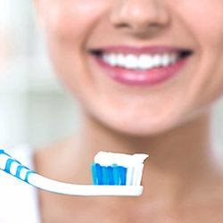 Woman smiling holding toothbrush