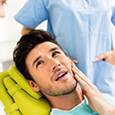 Male patient in dental chair holding cheek in pain