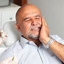 Older male dental patient holding cheek
