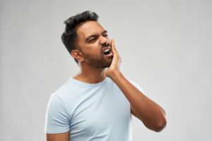 person holding their jaw because of a toothache