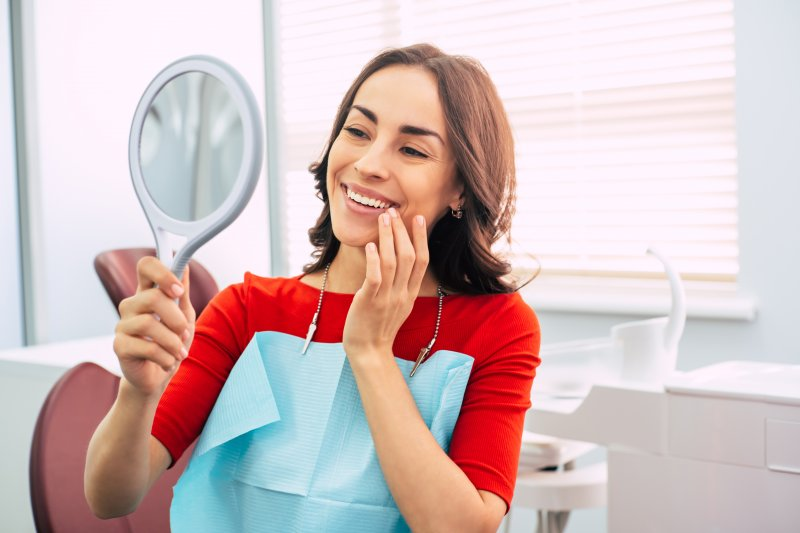 Woman smiling at reflection at dentist's office